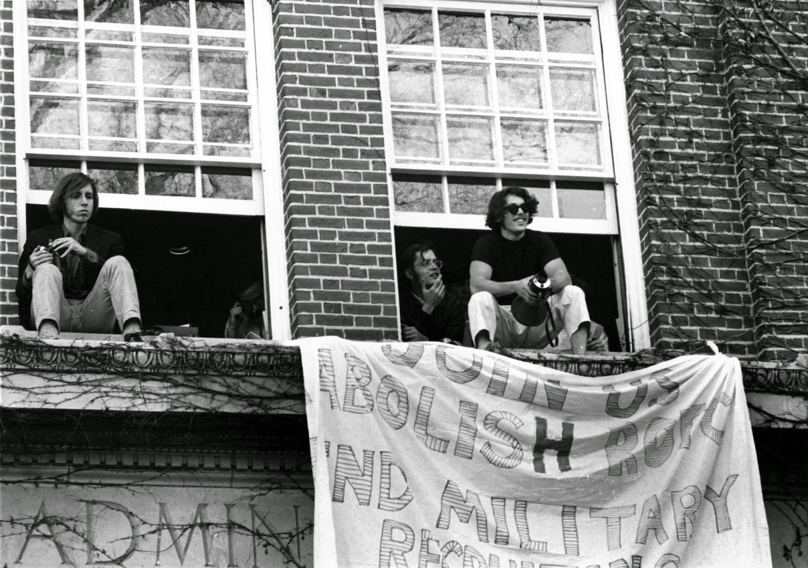 A photograph of students perched in open windows from which a hand-made banner hangs.