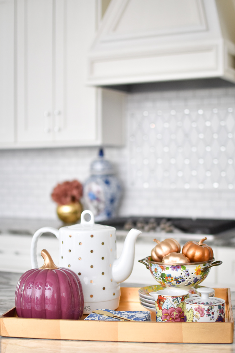 White kitchen with fall decor including metallic pumpkins, florals, ginger jars, and tobacco leaf china. #teaparty #kitchendesign #kittchendecor #whitekitchen
