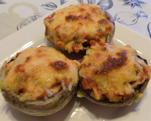 This is a picture of 3 mushrooms stuffed with sauce, pepperoni and cheese
