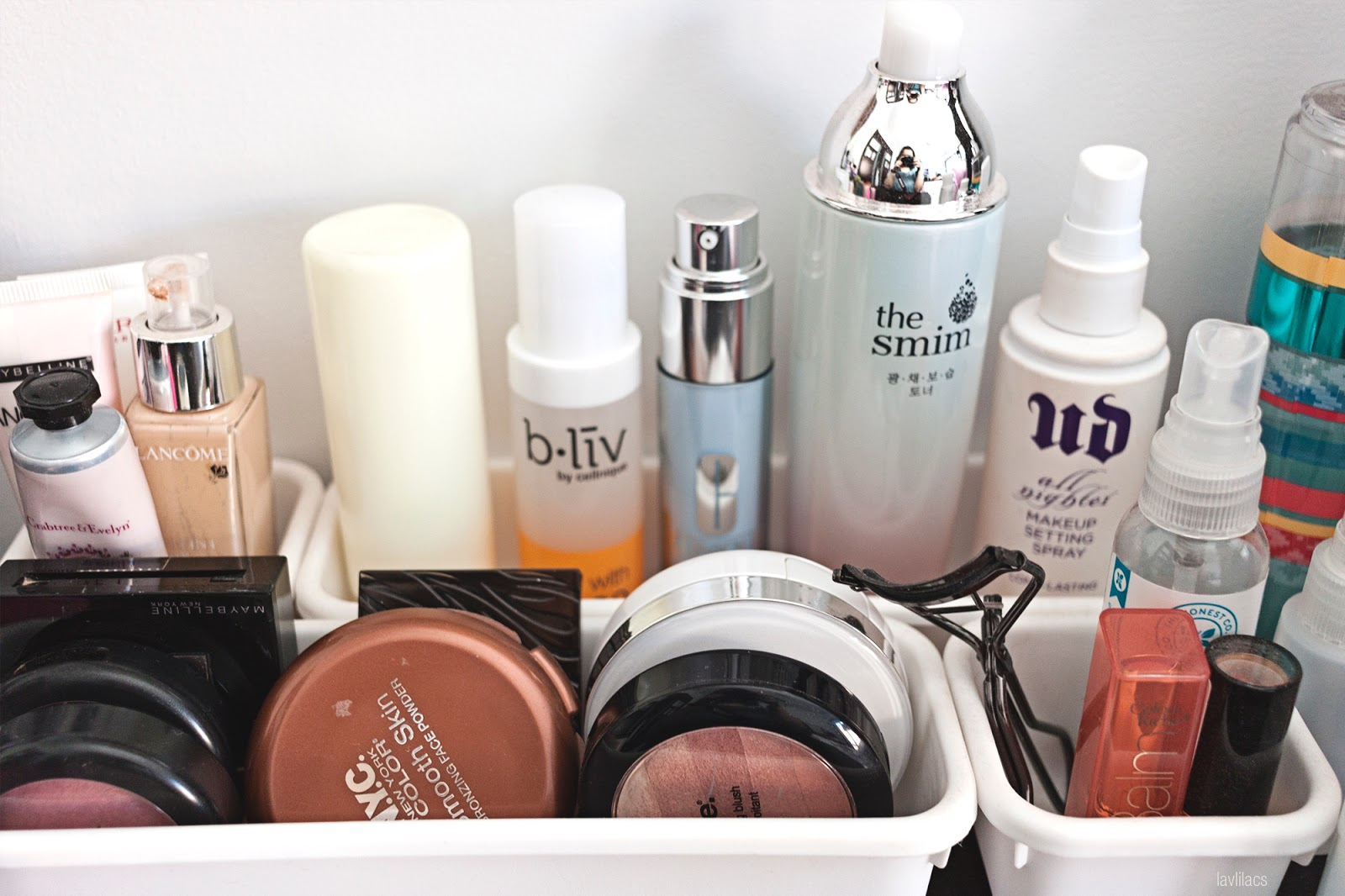 Daily makeup and bottled skincare products on top of bedside table