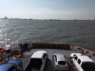 view from upper deck looking down at vehicles on the ferry  as it moves across the water