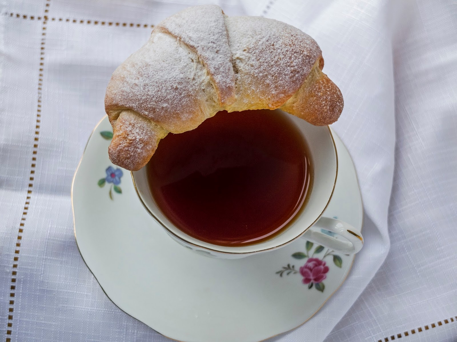 A yeast dough sweet bread sitting on the edge of a vintage teacup.