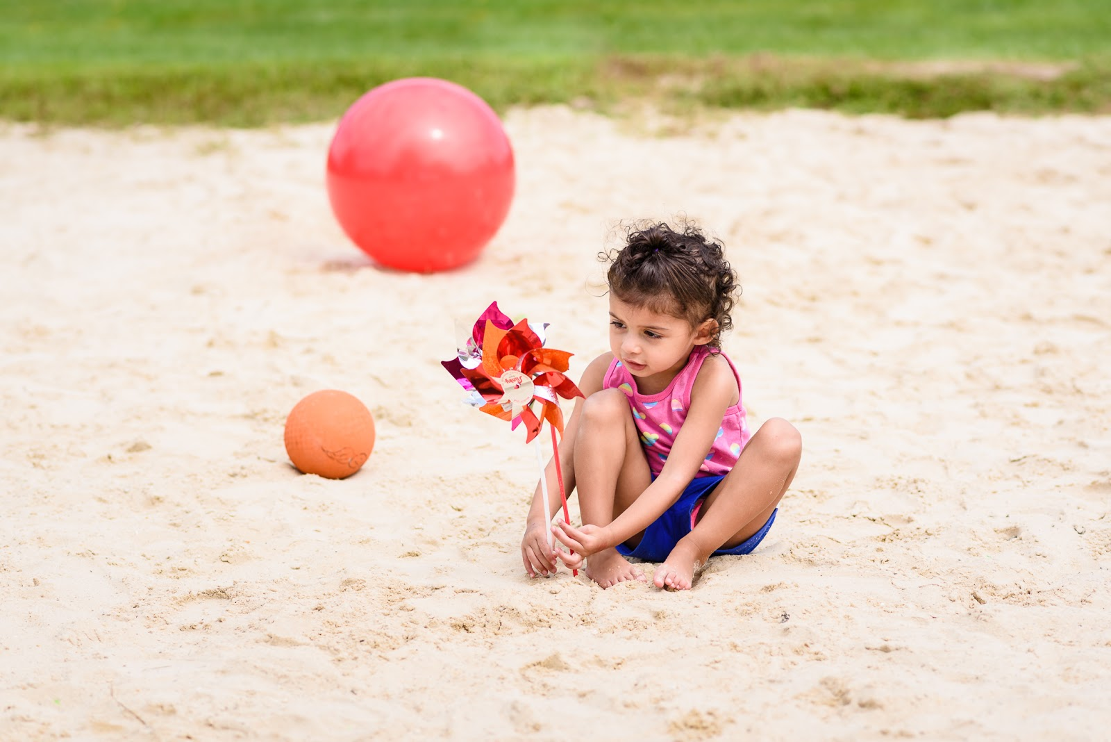 child playing with pinwheels in sand Music Together Vivo! Park Playalong © Diana Sherblom Photography