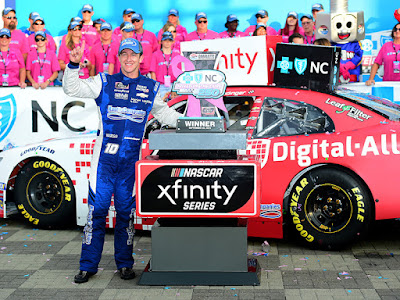 A J Allmendinger poses with the trophy in Victory Lane after winning the NASCAR Xfinity Series Drive for the Cure 250 presented by Blue Cross Blue Shield of North Carolina at Charlotte Motor Speedway.
