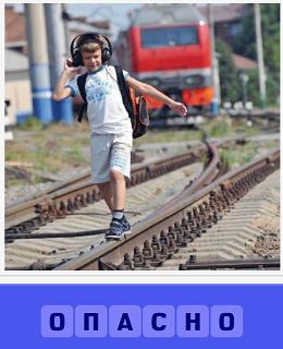 по рельсам идет мальчик в наушниках а сзади идет поезд