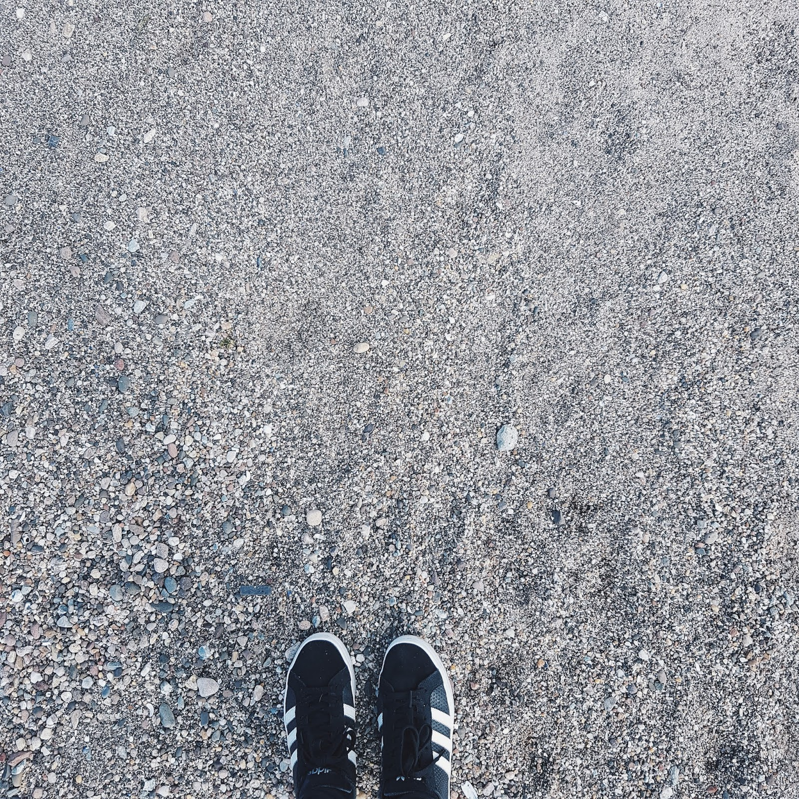 Shoes Stood on a Stone Beach