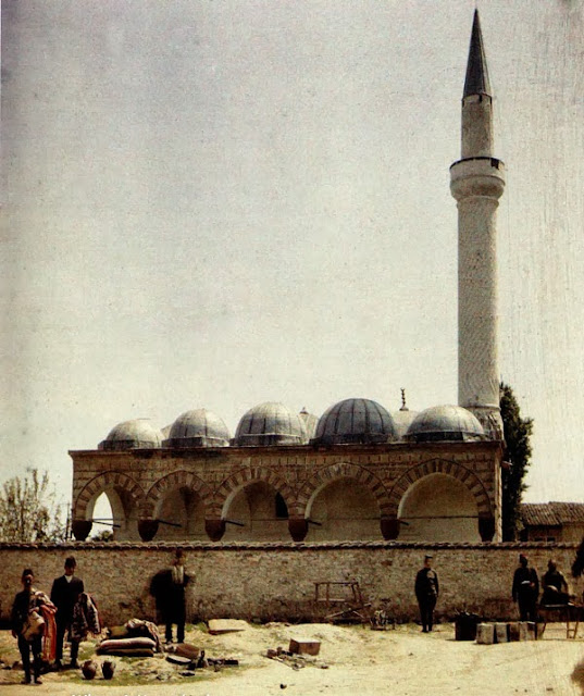 Burmali Mosque - Skopje in 1913. The facade of the mosque of Isak-bey, with a porch with five arches and five cupolas. The mosque is preceded by a courtyard surrounded by a wall, in front of which traders sell various goods. The mosque was built in 1475 by Isak-bey, in the style of the imperial mosques of Istanbul. The domed construction covered with lead is very interesting.