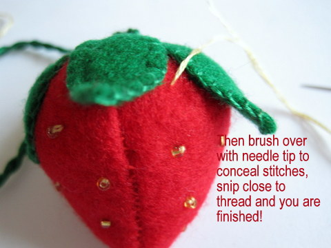 Felt strawberry finishing tutorial showing how to make this strawberry trimmed with gold beads
