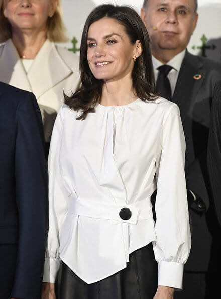 The Royal Tapestry Factory in Madrid. white belted button detail top, long sleeve asymmetric, white blouse, black leather midi skirt