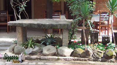 Detalhe da mesa de pedra com os pilares de pedra com o canteiro com pedras do rio e com pedra moledo, as bromélias com os troncos de dormente.