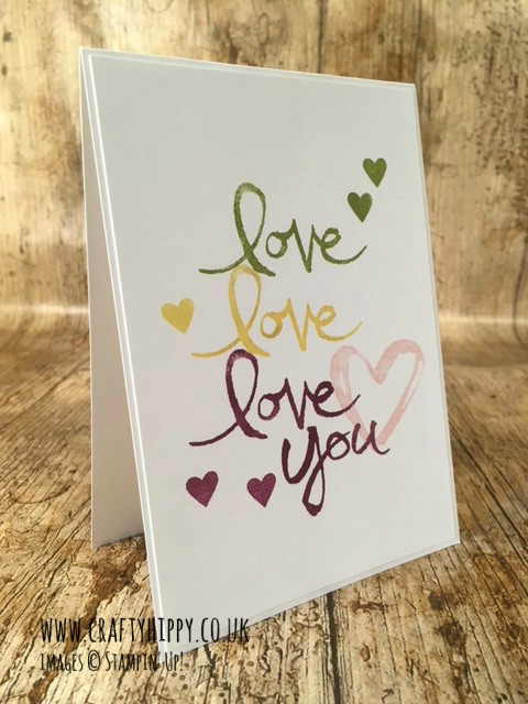 This image shows a white, hand stamped card made with Stampin' Up! products with the word Love stamped three times in Rich Razzleberry, Old Olive, and Daffodil Delight.