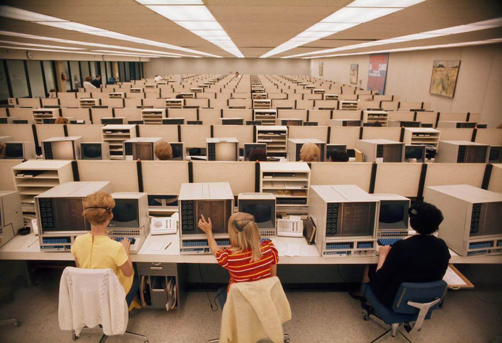 Women operators man computers at Eastern Airlines' reservations center in Miami, Florida. The woman in the centre-front wears a brightly striped top and very naturally styled hair, held loosely in a clip. The woman to the left wears a yellow cotton top and shoes. Cardigans are loosely flung over the backs of their chairs. 1970.