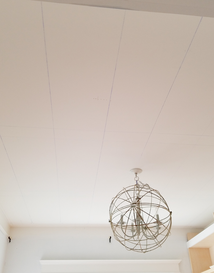 ceiling with marked joists and round chandelier.