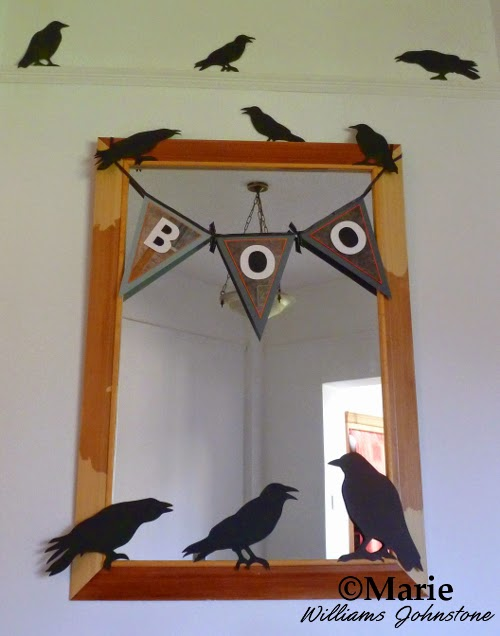 Decorated mirror with boo banner and black bird cut out decorations