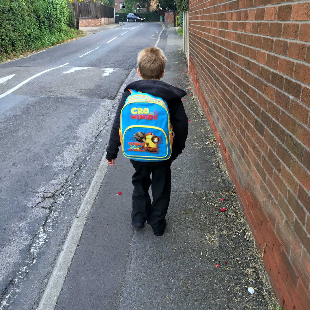 young boy with school bag on his back, walking to school