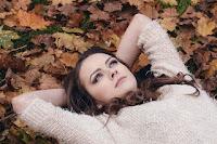Eine junge Frau, die auf einem mit altem Laub bedeckten Waldboden liegt und nachdenklich in den Himmel sieht