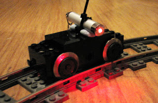 [Image: A LEGO train engine chassis on a curved LEGO track, with a little laser pointer attached to it using blu-tack and cable ties. The laser is emitting red light.]
