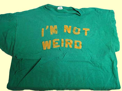 Green shirt with gold block letters reading I'M NOT WEIRD