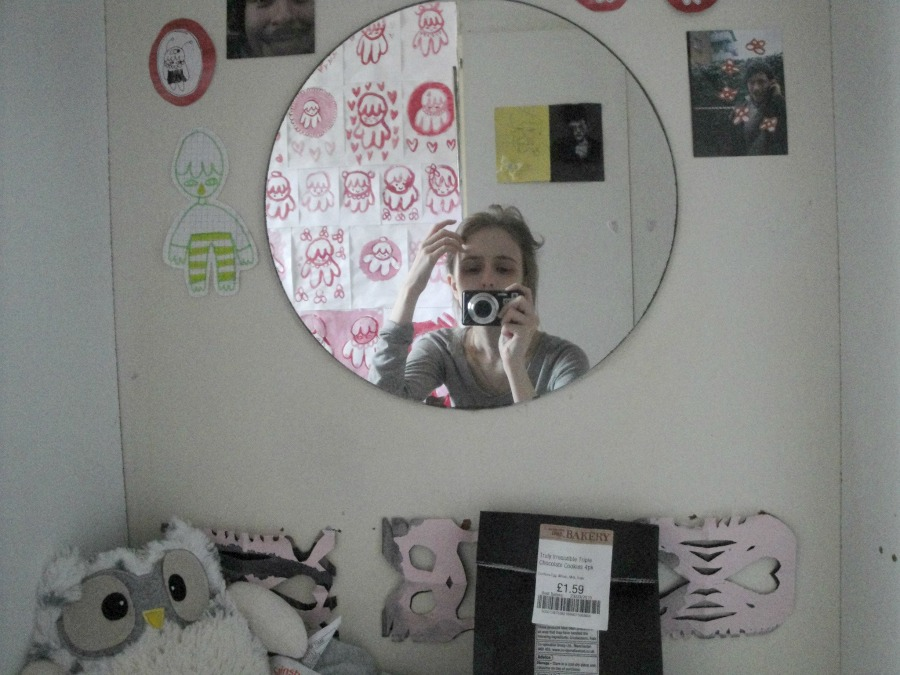 A picture showing me reflected in the circular mirror at my desk. Just below the mirror are a cuddly toy owl and a bag of cookies.
