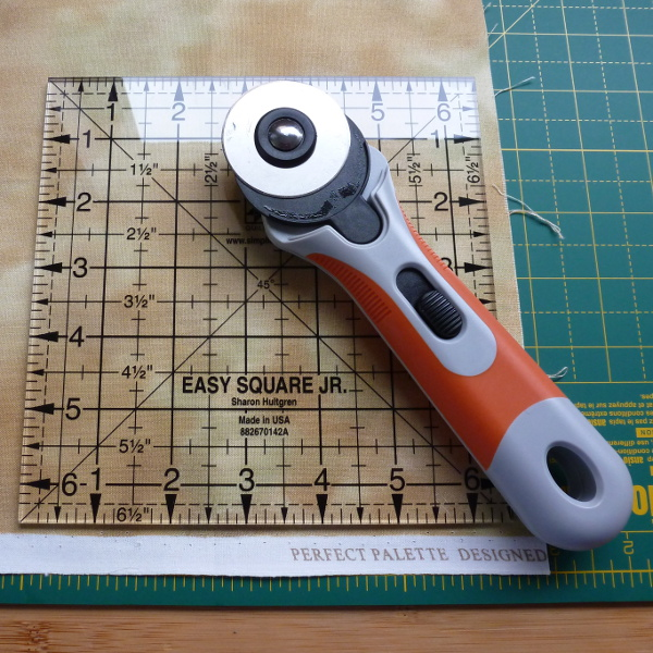 Fabric rotary cutter cutting around a square template over a self heal mat
