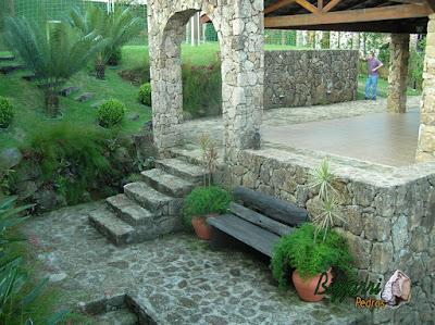 Construção do muro de pedra com pedras brutas com o piso de bruta com a escada de pedra, o pórtico de pedra com a escada de dormente de madeira e a execução do paisagismo em sítio em Mairiporã-SP.