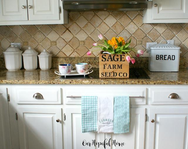 stencilled wood crate flowers tea cups tea towels bread box