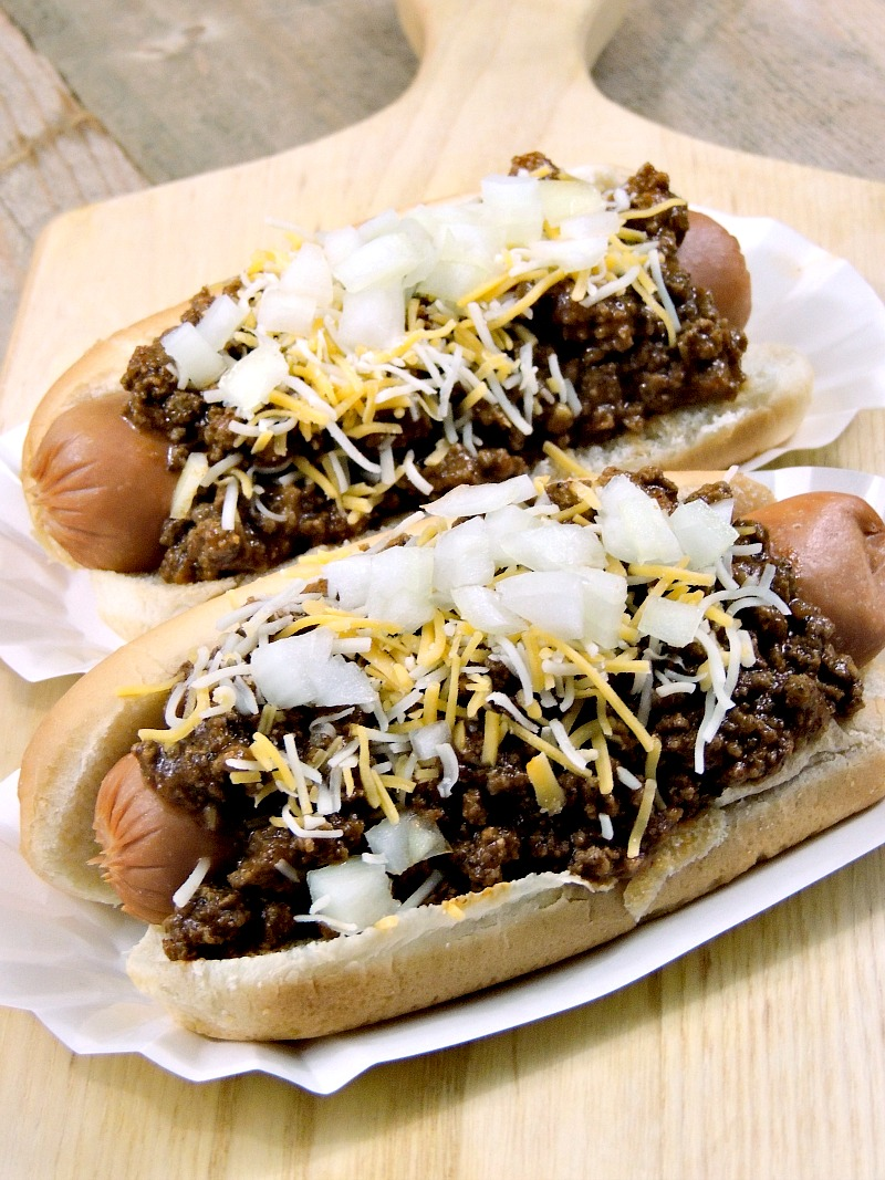 2 hot dogs with Coney Island Hot Dog Chili topped with chopped onions and shredded cheese on a cutting board with a red and white checkered napkin.