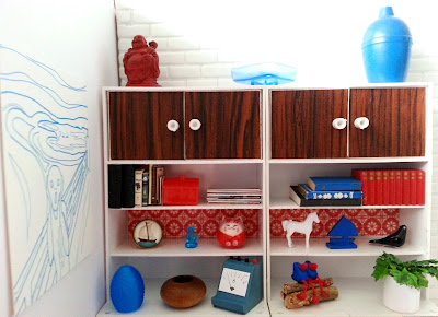 One-twelfth scale miniature retro woodgrain and white display units containing various objects in red, teal, white and black.