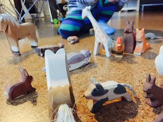 Das Kind spielt mit seinen Ostheimer Tieren: Pferde, Schwein, Hasen, Seehund, Eichhörnchen, Fuchs, Hahn, Giraffe