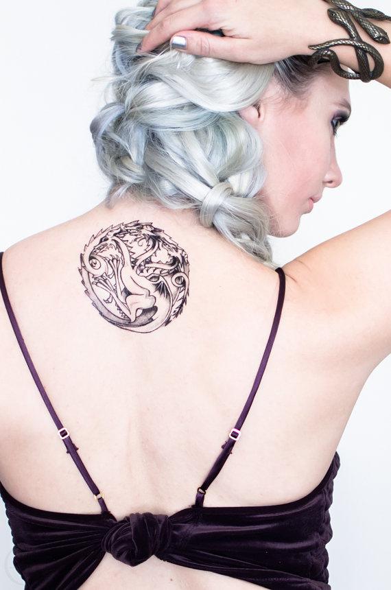 chica con el cabello blanco, lleva en la espalda un tatuaje de la casa Targaryen
