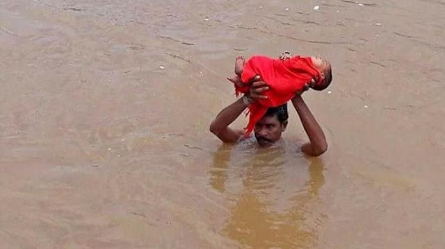 Sungguh Pahlawan, Ayah Ini Gendong Bayinya Saat Banjir Setinggi Leher