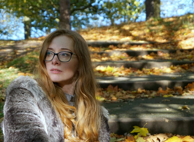 woman sitting outside in a park wearing a faux fur coat and looking off camera