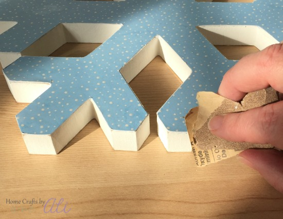 sanding edges of wood snowflake decoration