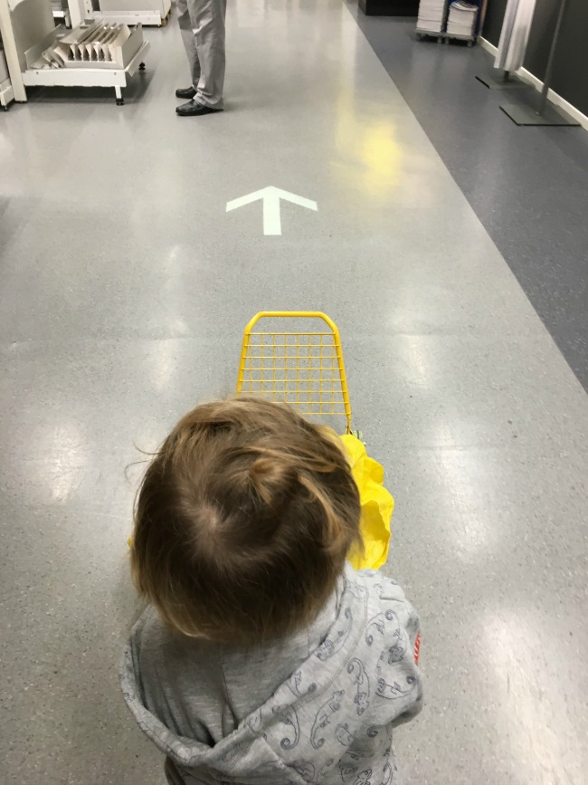 toddler-pushing-trolley-towards-arrow-in-ikea