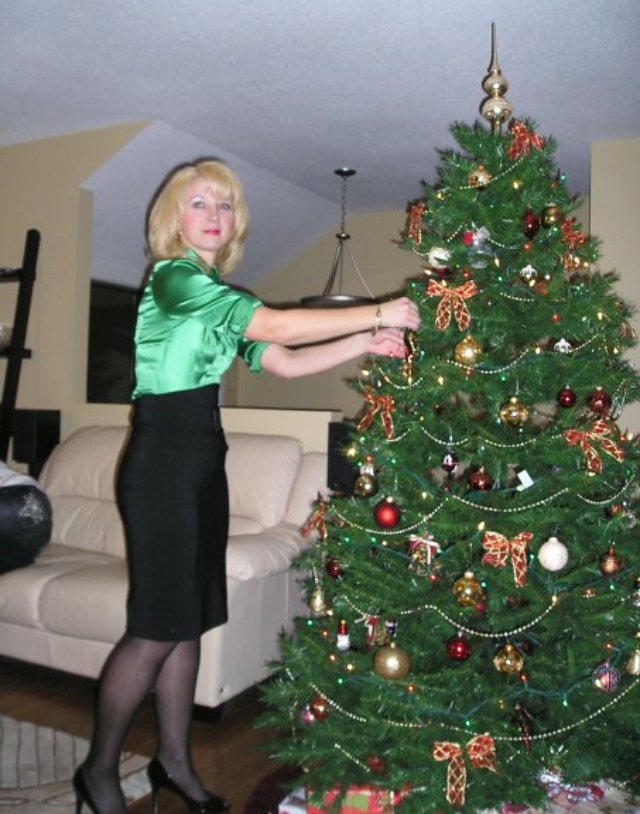A middle aged woman in green silk shirt decorates the Christmas tree