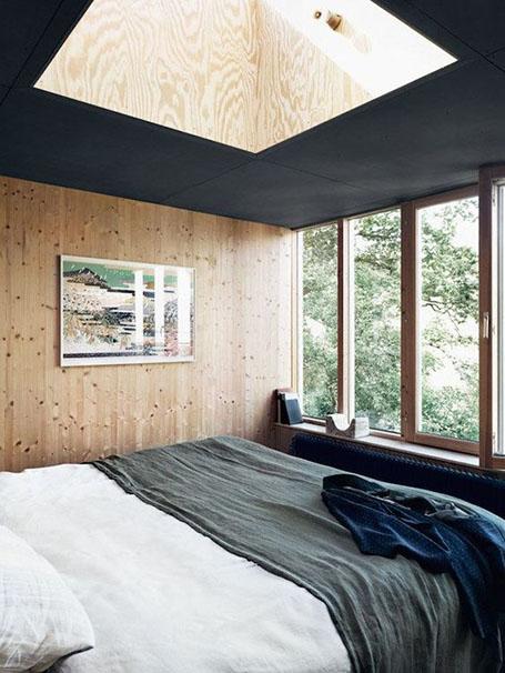 Décoration style scandinave murs en pin plafond noir puits de lumière