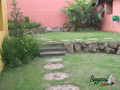 Muro de pedra rústica com tipo de assentamento rústico com a escada de dormente com execução do paisagismo em sítio em Mairiporã-SP.
