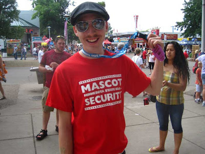 Young man in red tshirt with white letters reading Mascot Security Team