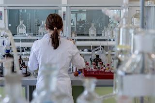 Química: Señora con bata blanca trabajando en el laboratorio de química.