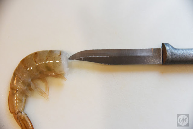 Where to insert a knife while deveining shrimp