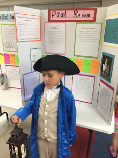 Young boy dressed at Paul Revere wearing a black hat, blue jacket and holding a lantern