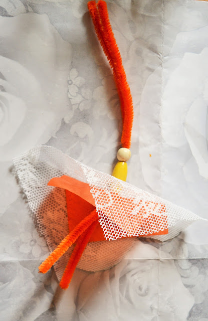 Pipe cleaners through tissue paper and beads