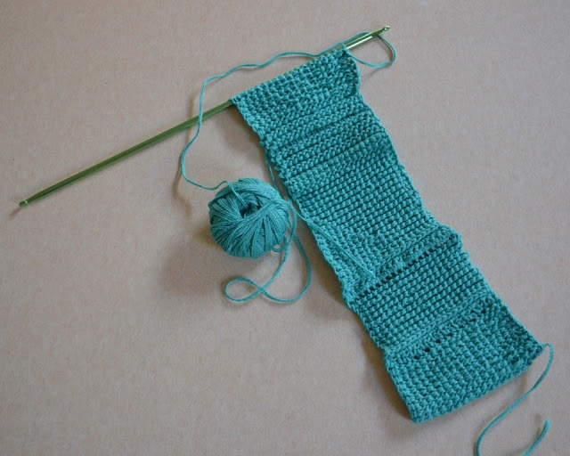 The reverse side of the test swatch. The double-ended hook is at the top and the ball of cotton is next to the sample.