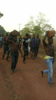 Two men forced to carry rocks on their heads after being caught stealing (Photos)