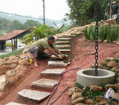 Escada de pedra cacão Goiás com tamanho entre 0,40 a 1,00 m e espessura entre 6 a 10 cm. Escada de pedra assentada com cimento, areia e  terra com junta de grama preta e com a execução do paisagismo na lateral da escada.
