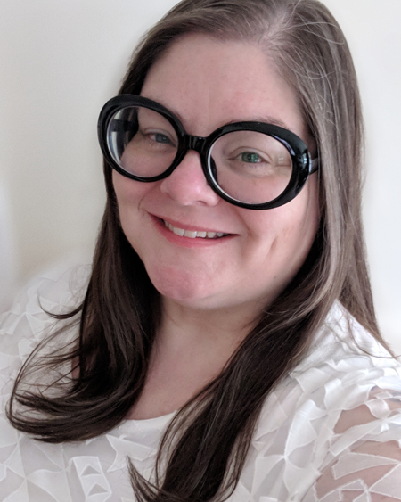image of me from the shoulders up, wearing large black-framed glasses and a white top, with my hair down