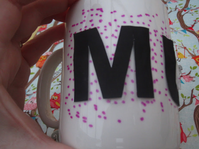 Mug being decorated around the lettering