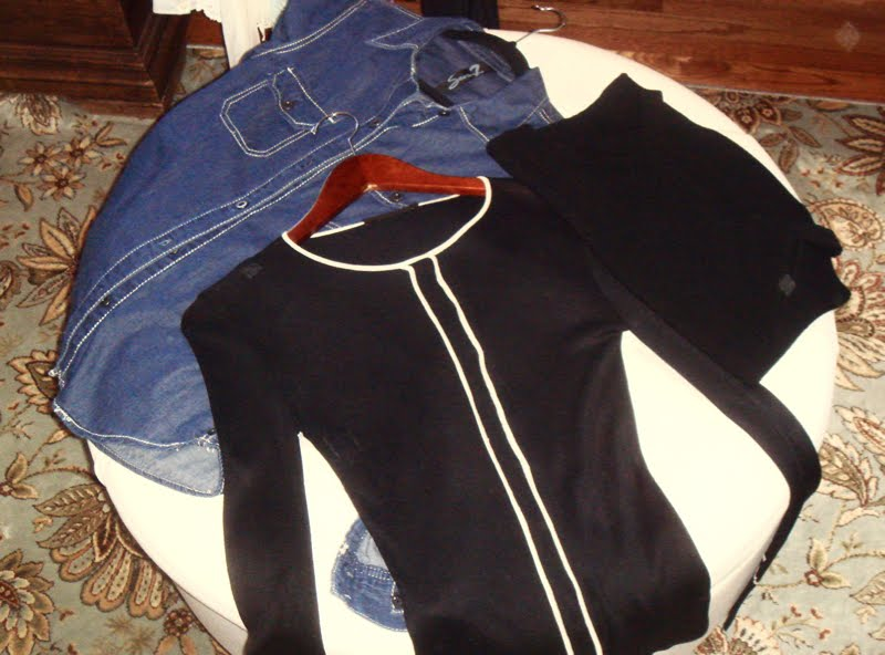 Tops laid out on ottoman. A jean shirt, a super lightweight black cardigan,and a black sleeveless top.