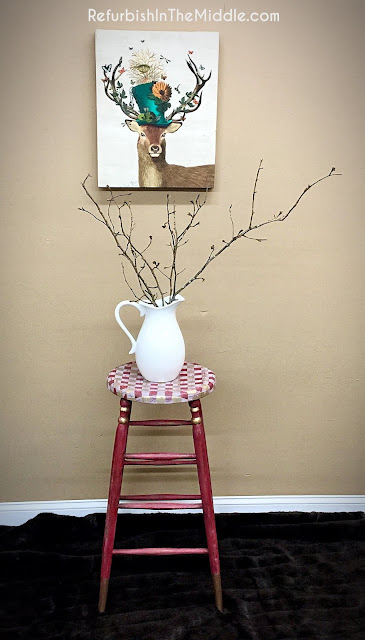 white ceramic vase sitting on top of a red stool with red, white and gold gingham next to a trendy deer picture