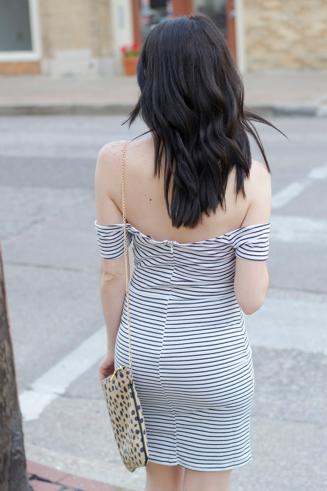 Walking in the city wearing a striped body con off the shoulder dress with loose curls